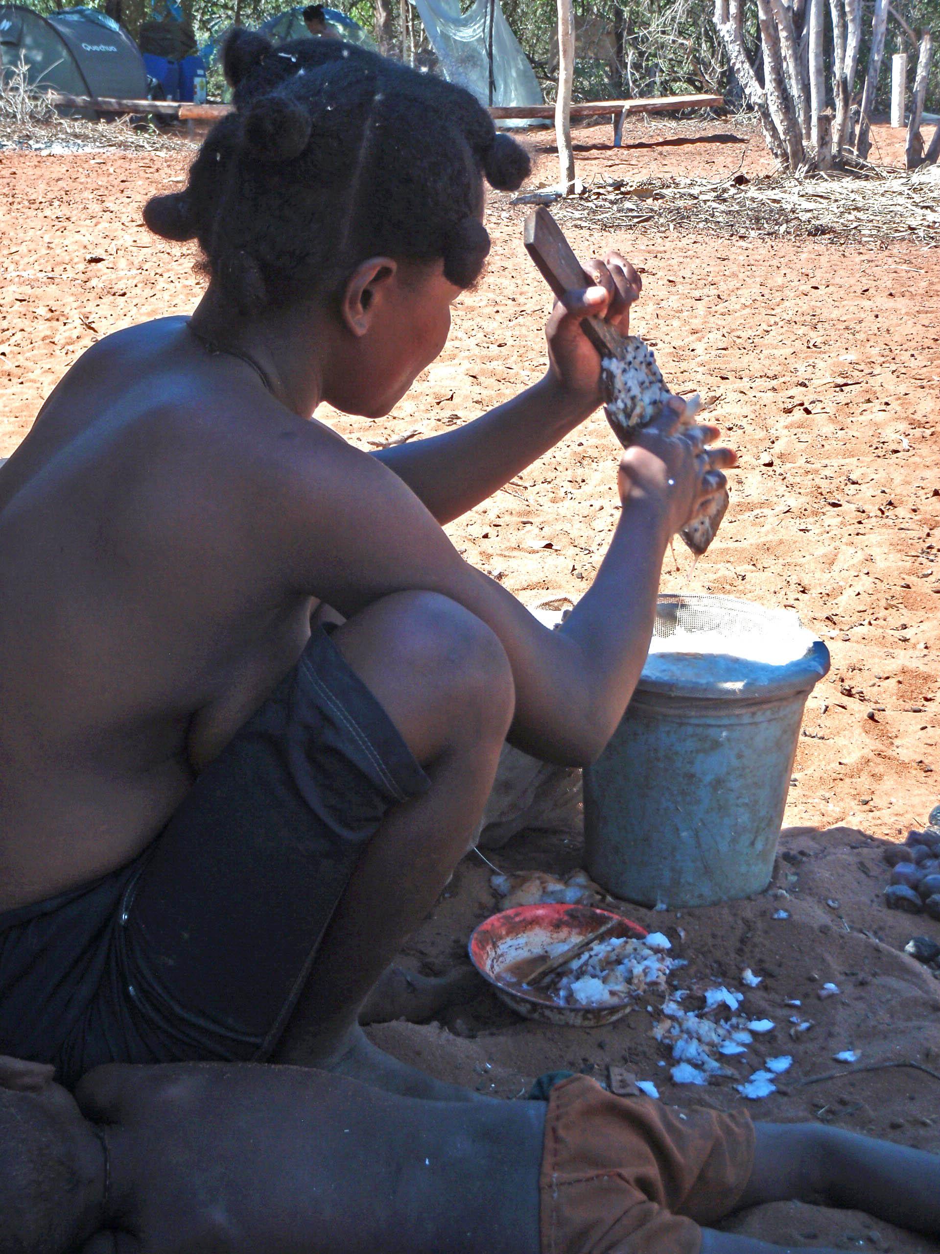 Nanao qui rape le babo Elle rappe le babo pour en extraire le jus, avec ce jus, elle fera cuire un peu de maïs pour ses enfants.